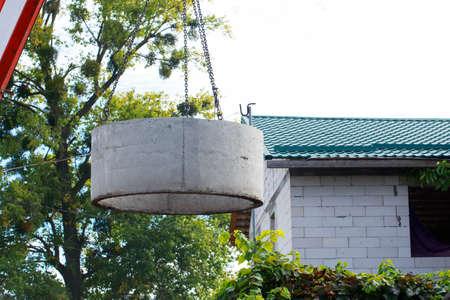 Crane with hooks raises heavy concrete structure Imagens - 124883573