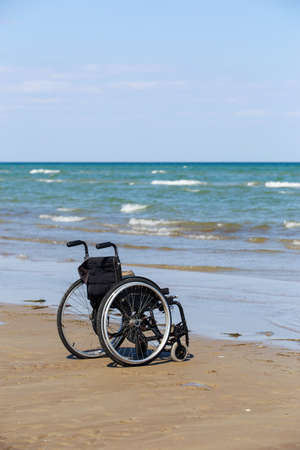 Empty black wheelchair stands on the seashore