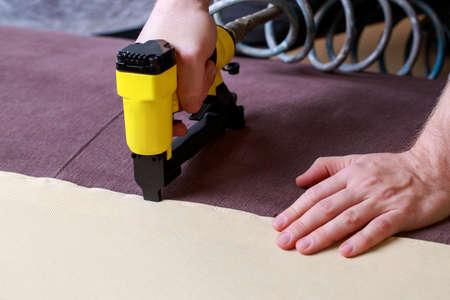 Restoring old sofa upholstery using a pneumatic stapler