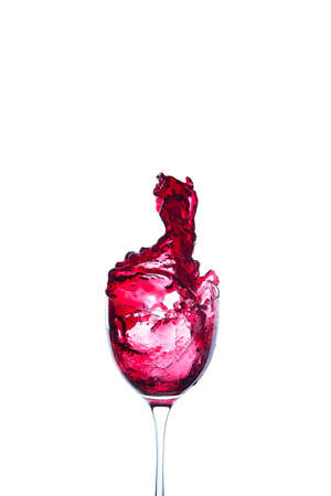 red wine is poured into a glass on the white background