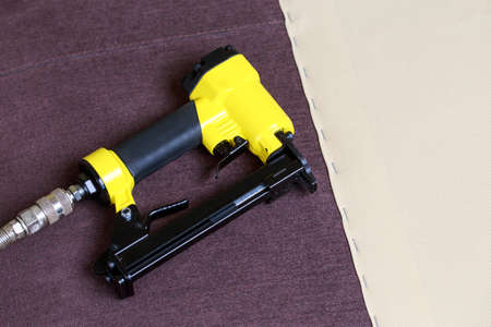 The pneumatic stapler lies on brown upholstery