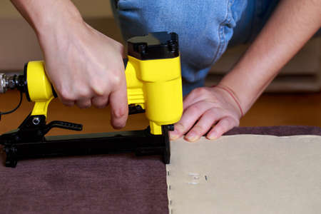 Restoring old sofa upholstery using a pneumatic stapler 免版税图像
