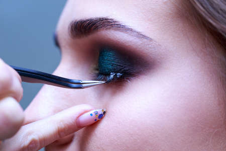 Beautician performs eyelash extension procedure a close up