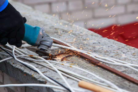 The worker cuts metal using angle grinder