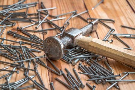unas largas: Martillo sucia y las u�as largas en el fondo de madera Foto de archivo