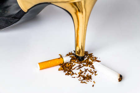malos habitos: world no tobacco day concept, shoe put on Broken cigarette on white background.