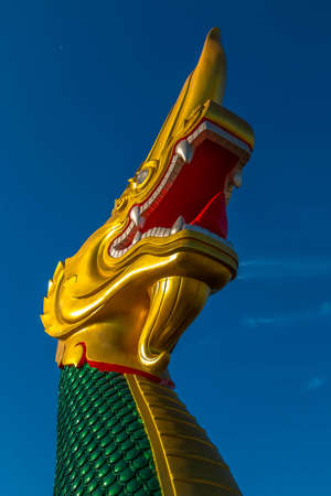 Biggest Magnificent statue Green and shiny  gold Naga , Fairy tail animal in asia religion at navy blue sky. Stock Photo