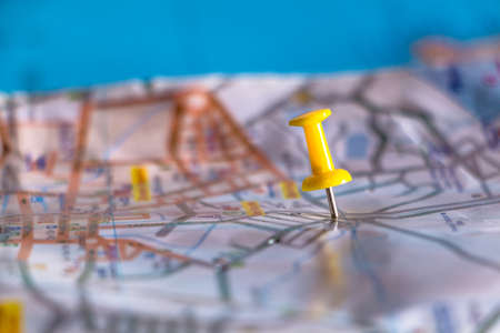 Travel destination pin points on a map with colorful thumbtacks and depth of field with select focus.