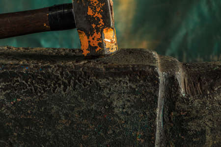 antique factory: The blacksmith manually forging the molten metal on the anvil in smithy Stock Photo