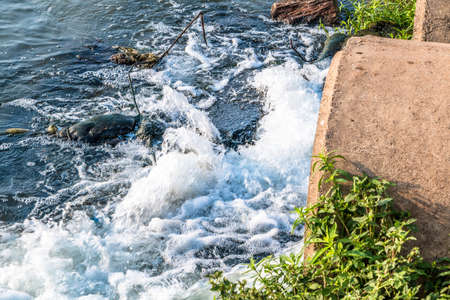 Unclean water from the sewer flows into the river. Stock Photo