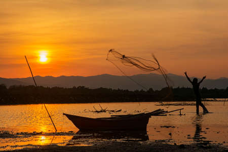 silhouette fishing man and sunset in Thailand photo