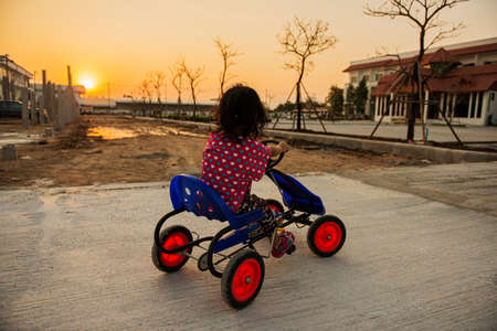 four wheel: cute little curly girl riding a four wheel bicycle Stock Photo