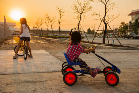 two little girl riding a bicycle in sunset ,Thailand photo