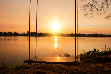 river side: lone swing at river side and sunset ,Thailand Stock Photo