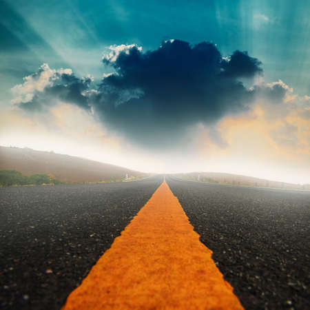 long road: Long road and dramatic sky with sunray. Stock Photo