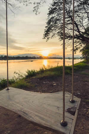 river side: lone swing at river side and sunset Thailand . Vintage Tone.