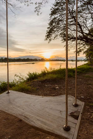 river side: lone swing at river side and sunset Thailand
