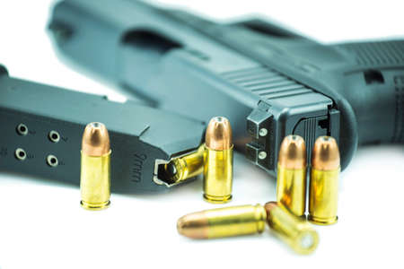 violence in sports: 9mm bullets and black gun pistol isolated on white background.