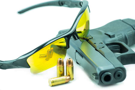 violence in sports: Orange sun glasses and 9mm black gun pistol isolated on white background.