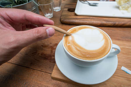 energizing: Empty coffee cup after drink with spoon on wood table.