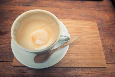 stimulating: Empty coffee cup after drink with spoon on wood table.