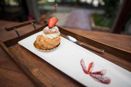 choux: fresh strawberry Choux Cream on wooden tray. Stock Photo