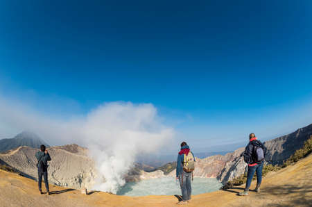 Tourists taking photograph at Kawah Ijen Crater at sunrise panoramic view, Indonesia. Фото со стока