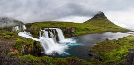 Panoramic view of Kirkjufellfoss and Kirkjufell mountain in cloudy day ,Iceland.