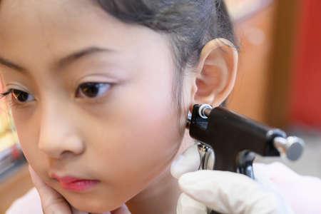 Adorable little Asian girl having ear piercing process. Stock Photo