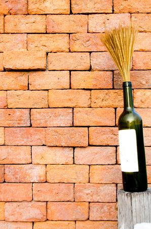 Wine with wheat on orange brick wall photo