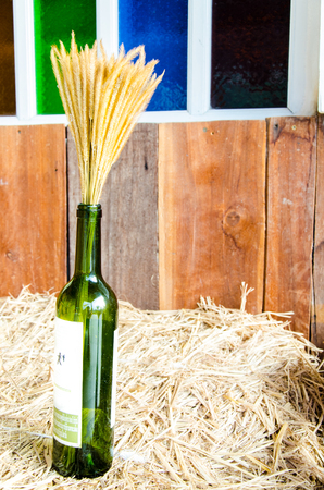 Wine with wheat on dry hay and mosaic window  photo