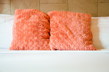 Pink and white puff pillows on white bed photo