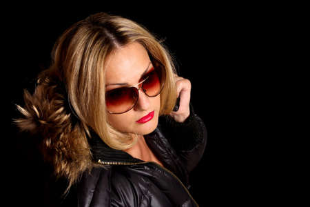 girl in sunglasses and jacket with fur hood Stock Photo