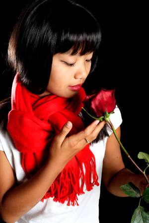 Asiatische M�dchen in einem roten Schal mit einer roten Rose