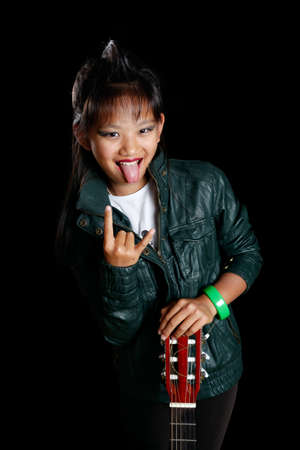 rocker girl shows tongue and horns with his fingers Stock Photo