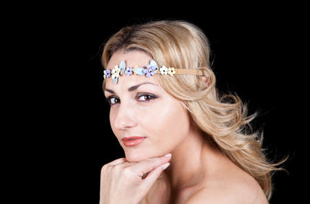 Smiling young girl in a Greek style with a rim of flowers on her head  Stock Photo