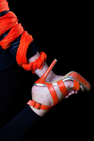 heelpiece: woman s hand, wrapped in an orange scarf, holding a leg in an orange shoe