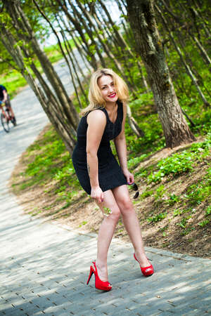 Portrait of a smiling beautiful girl in nature  In a black dress and red shoes  photo