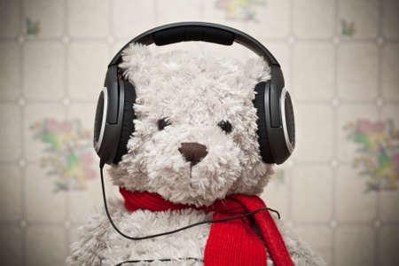 Spielzeug Teddyb�r mit einem roten Schal auf Musikh�ren �ber Kopfh�rer