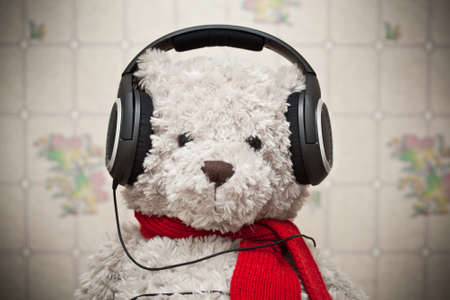 Toy teddy bear with a red scarf listening to music on headphones photo