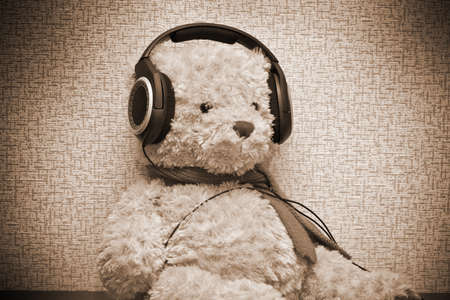 Teddy bear listening to music on headphones. Photo by sepia toned photo