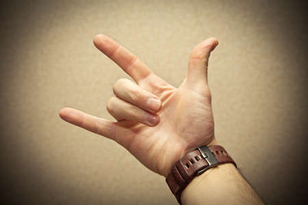 Fingers to show metal goat. watch on hand. photo toned yellow photo
