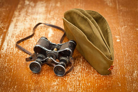 forage: Military binoculars, forage cap with a red star. Victory Day on May 9. Retro style Stock Photo