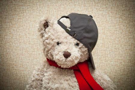 Teddy in tragen einen roten Schal und eine schwarze Baseballm�tze. Babypl�schspielzeug
