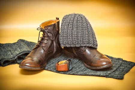 Fashion leather shoes, wristwatch knitted scarf and hat. Yellow abstract background