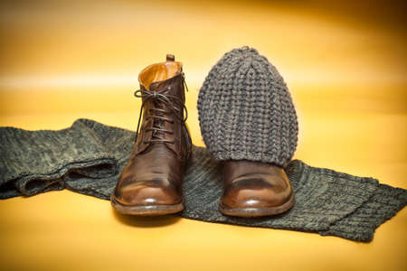 Brown fashion leather shoes, knitted scarf and cap on an abstract background yellow. still life of clothes