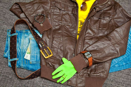 leather jacket, T-shirt, jeans with a leather belt, watches, bracelets, sunglasses and gloves. Banknote 5 Euro