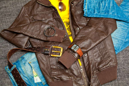 fashionable unisex outfit: leather jacket, T-shirt, jeans with a leather belt, watches, bracelets, sunglasses. Banknote 5 Euro