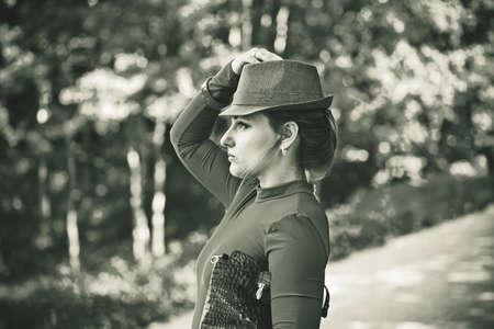 Portrait eines M�dchens im Freien in einem Kleid, Hut und Tasche. Vintage-Stil