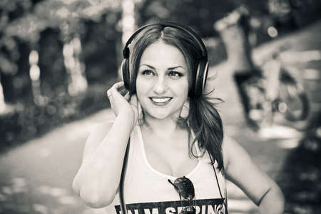 Portrait of a beautiful young smiling girl outdoors in a T-shirt, listening to music on headphones Stock Photo